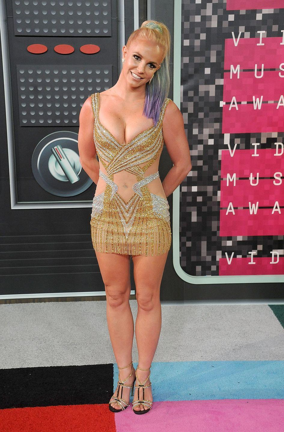 <p>Here, Britney poses in a sparkly gold mini with see-through fabric and a sweetheart neckline. She also had a dyed ponytail that's making me want to make a hair-color appointment, stat. </p>