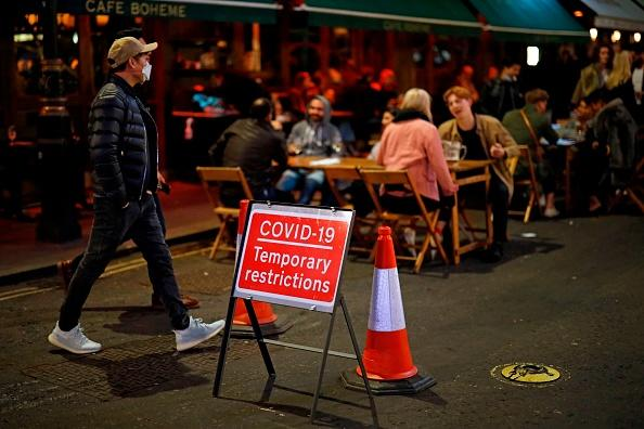 People drink at the outside tables of a cafe in Soho, in central London.