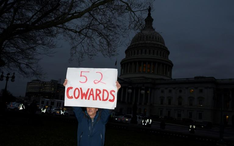 A protester holds up a sign outside the Capitol in Washington after a majority of 52 Republican senators voted to acquit the president of abuse of power