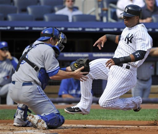 New York Yankees' Robinson Cano, right, scores on a sacrifice fly by Curtis Granderson as Toronto Blue Jays catcher Jeff Mathis fields the throw during the first inning of the first baseball game of a doubleheader, Wednesday, Sept. 19, 2012, at Yankee Stadium in New York. (AP Photo/Bill Kostroun)