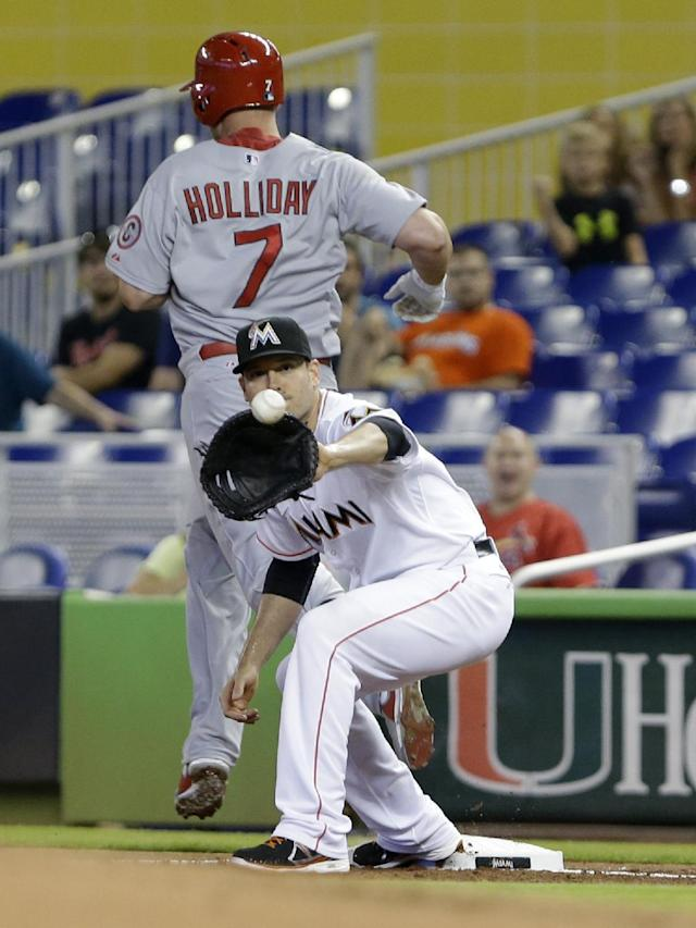St. Louis Cardinals' Matt Holliday (7) reaches first base safely as Miami Marlins first baseman Greg Dobbs fields the throw during the first inning of a baseball game, Saturday, June 15, 2013 in Miami. (AP Photo/Wilfredo Lee)