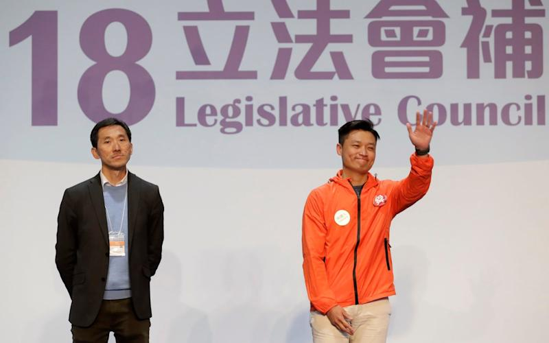Hong Kong pro-Beijing by-election candidate Vincent Cheng Wing-shun waves next to his pro-democracy competitor Edward Yiu after winning a seat at the legislative council - AP