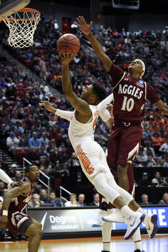 Clemson guard Shelton Mitchell (4) shoots as New Mexico State forward Jemerrio Jones (10) defends during the first half of a first-round NCAA college basketball tournament game Friday, March 16, 2018, in San Diego. (AP Photo/Denis Poroy)