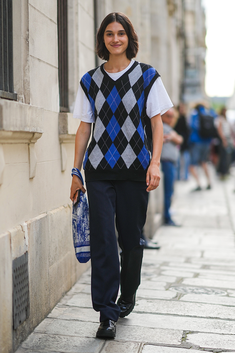 <p>The sweater vest strikes again, this time layered over a classic white tee and paired with navy work trousers.</p>