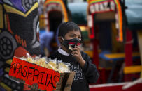 A child, wearing a protective face mask, hawks bags of potato chips near a row of painted wooden boats known as trajineras, popular with tourists that ply the water canals in the Xochimilco district of Mexico City, during a reopening of activities after a six-month pause due to the COVID-19 pandemic. (AP Photo/Marco Ugarte)