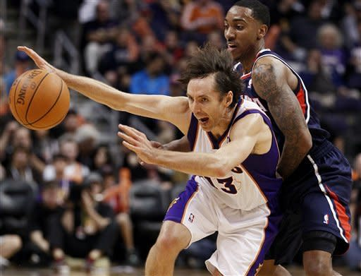 Phoenix Suns' Steve Nash (13) chases down the loose ball as Atlanta Hawks' Jeff Teague defends during the second half of an NBA basketball game on Wednesday, Feb. 15, 2012, in Phoenix. (AP Photo/Matt York)