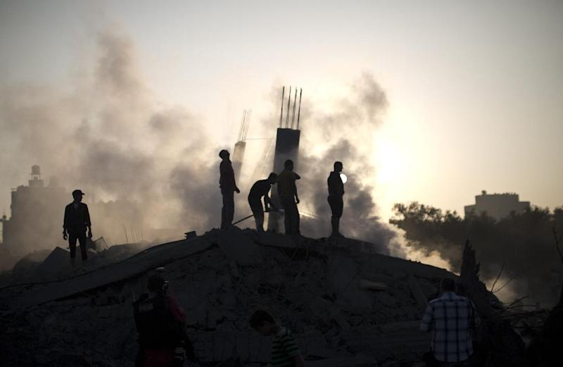 Palestinian men inspect the site of an Israeli military strike in Gaza City on July 8, 2014 (AFP Photo/Mahmud Hams)