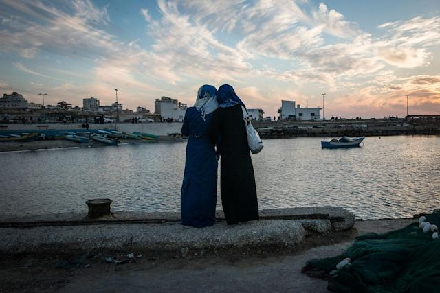 <p>Girls watch the sun set at the harbor in Gaza City. While living in Gaza is undeniably tough, being a woman there is harder. (Photograph by Monique Jaques) </p>