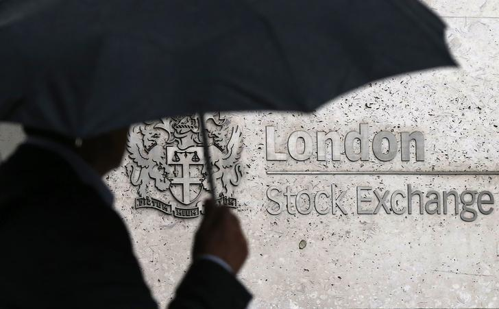 FILE PHOTO: A man shelters under an umbrella as he walks past the London Stock Exchange in London, Britain August 24, 2015. REUTERS/Suzanne Plunkett