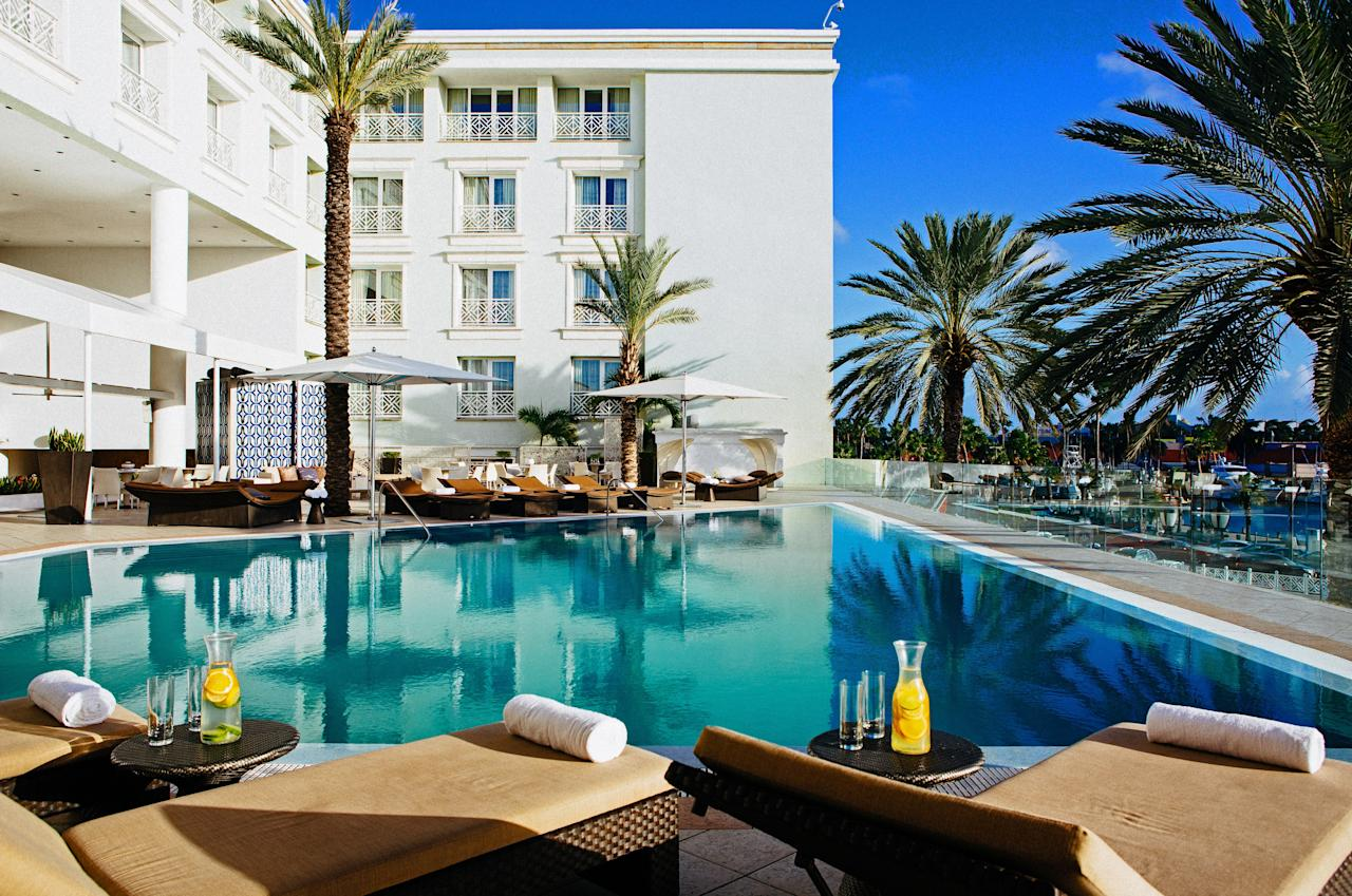 """Located in downtown Oranjestad, the <a href=""""https://www.marriott.com/hotels/travel/auabr-renaissance-aruba-resort-and-casino/"""" target=""""_blank"""">Renaissance Aruba</a> is divided in two: one side for <a href=""""https://www.cntraveler.com/story/complete-guide-to-family-travel?mbid=synd_yahoo_rss"""">families</a> and one side for adults. Hop aboard a water taxi for exclusive and complimentary access to the resort's own 40-acre private island. The beachfront day resort has thatched-roof cabanas with over-the-water hammocks and, just like the hotel, the private island is divided into a family fun beach and a tranquil, adults-only beach."""