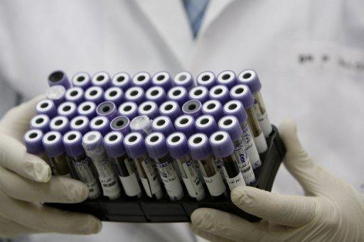 This file photo shows a genetic researcher carrying blood samples. As athletes get ready to smash Olympic records in London, scientists are in a high-stakes race of their own to develop a test that will unmask anyone altering their genes in a desperate quest for gold