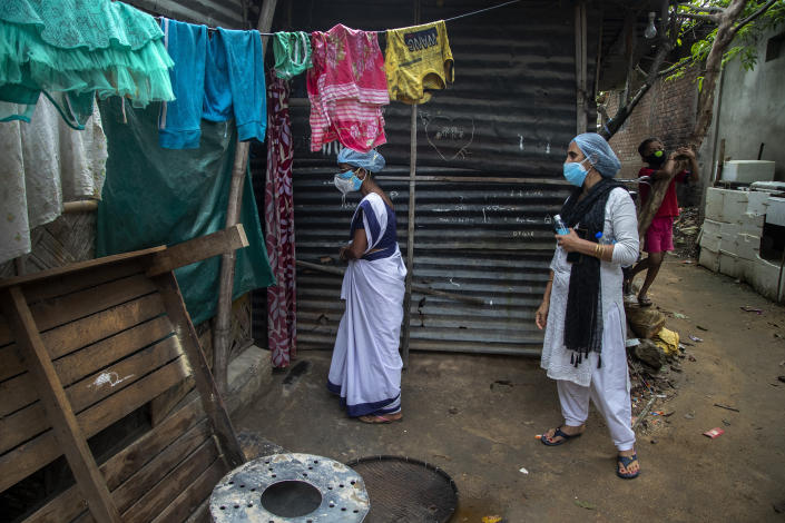 Heath workers call a woman, unseen, who does not agree to give swab sample to test for COVID-19 in a slum in Gauhati, Assam, India, Monday, May 17, 2021. (AP Photo/Anupam Nath)