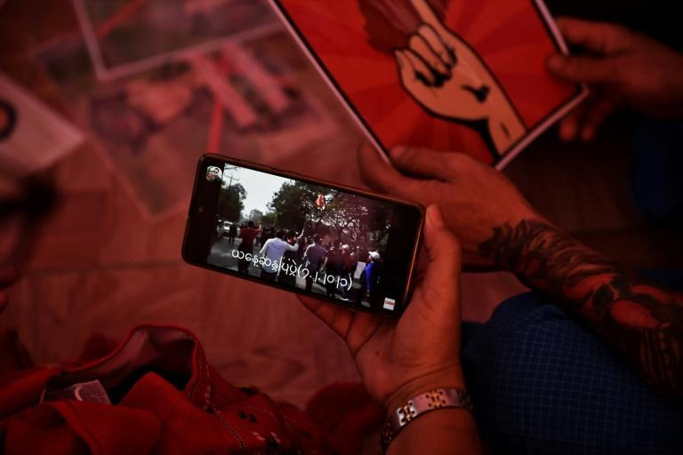 Myanmar migrants in Bangkok watch footage of mass protests in Yangon, as they gather together before going to a protest against the military coup back home