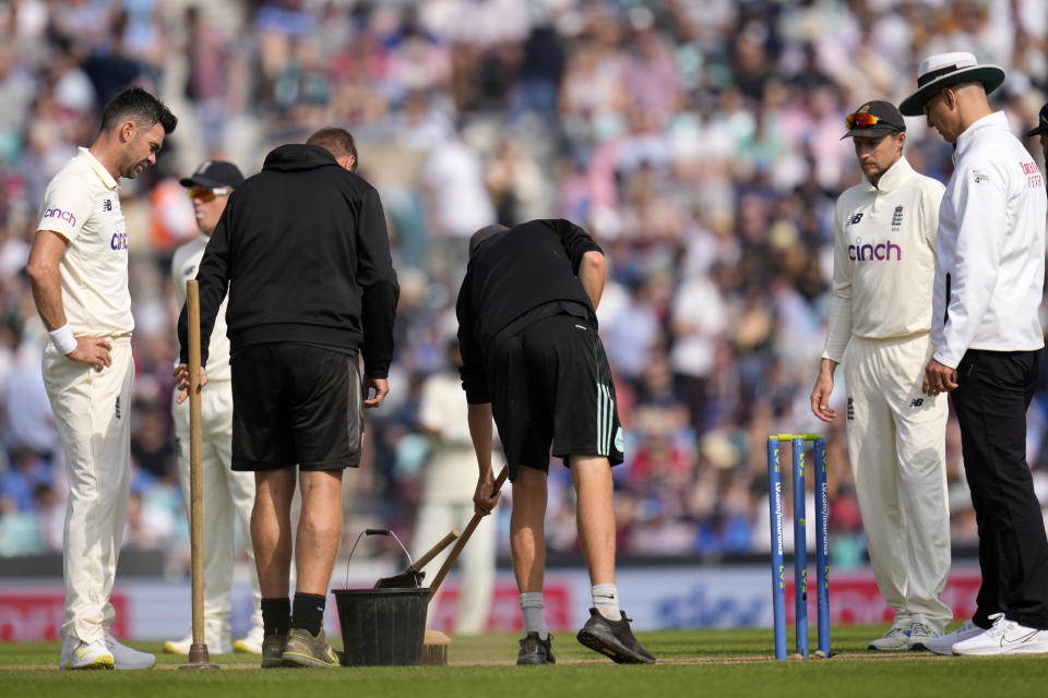 England's James Anderson watches as ground staff tend to the pitch on day four of the fourth Test match at The Oval cricket ground in London, Sunday, Sept. 5, 2021. (AP Photo/Kirsty Wigglesworth)