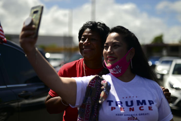 (From the left) conservative senator Nayda Venegas and Frances Lee, supporters of president Donald Trump, pose for a selfie moments before leaving for the headquarters of the Republican party in support of his candidacy a few weeks before the presidential election next November, in Carolina, Puerto Rico, Sunday, Oct. 18, 2020. President Donald Trump and former Vice President Joe Biden are targeting Puerto Rico in a way never seen before to gather the attention of tens of thousands of potential voters in the battleground state of Florida. (AP Photo/Carlos Giusti)