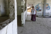 Devla Ajsic walks through the ruins of a former battery factory in Potocari near Srebrenica, Bosnia, Wednesday, July 7, 2021. Ajsic was 21 years old and three months pregnant in July 1995 when she was sexually assaulted in Srebrenica, eastern Bosnia, while her fiance and thousands of other men and boys were taken away and executed in Europe's only acknowledged genocide since World War II. (AP Photo/Eldar Emric)