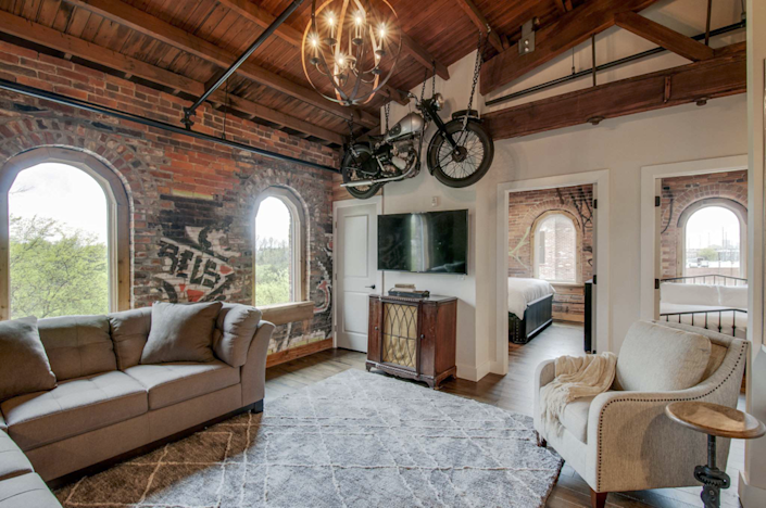 """Located inside a historic building built in 1865 during the Civil War is the ideal home-away-from-home for those enamored by both Nashville's charm and its grit. This top-floor condo features vaulted ceilings with original cedar beams and exposed brick walls. Don't forget to take a peek at the graffiti scattered along the walls from when the building was unused. Tucked away in an industrial area of town, this Airbnb is surrounded by several great neighborhoods, such as the Nations and Germantown. This semi-residential spot provides easy access to the endless bars, cafés, and restaurants located in nearby areas. $225, Airbnb. <a href=""""https://www.airbnb.com/rooms/43831509?source_impression_id=p3_1618343417_dXQzk7z0vzAtL2%2BU"""" rel=""""nofollow noopener"""" target=""""_blank"""" data-ylk=""""slk:Get it now!"""" class=""""link rapid-noclick-resp"""">Get it now!</a>"""