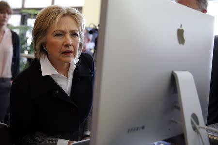 U.S. Democratic presidential candidate Clinton looks at a computer screen during a campaign stop at Atomic Object company in Grand Rapids