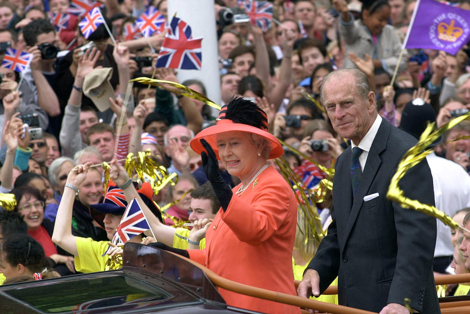 Queen Elizabeth II and her husband, Prince Philip, ride along The Mall in an open-top car as they return to watch a parade outside Buckingham Place. The parade, which lasted more than three hours, included processions by the Notting Hill Carnival, the Commonwealth and children from the Chicken Shed Theatre Company. The Queen is waving to the crowds that have gathered to greet her. (Photo by © Pool Photograph/Corbis/Corbis via Getty Images)
