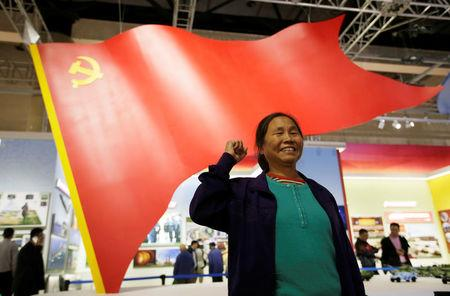 A visitor, a member of the Communist Party of China (CPC), poses for a photo during an exhibition displaying China's achievements for the past five years, as a part of the celebrations of the upcoming 19th National Congress of the Communist Party of China (CPC) at Beijing Exhibition Centre in Beijing, China October 10, 2017. REUTERS/Jason Lee