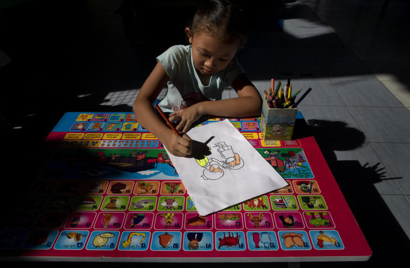 Warisara Klawkla, a daughter of teacher Watcharee Klawkla, colors a drawing made to educate children on COVID-19 prevention methods while her mother help cooking a meal at Makkasan preschool in Bangkok, Thailand, Wednesday, June 24, 2020. The teachers, many of whom are from the community, are eager to have the children back in the classroom but recognize the challenges posed by social distancing active preschoolers in a compact facility in this densely populated community. (AP Photo/Gemunu Amarasinghe)