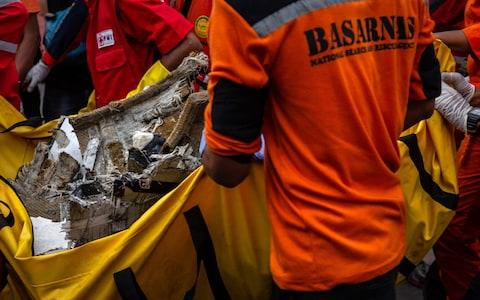 Search and rescue personnel examine recovered debris and personal items from Lion Air flight JT 610 - Credit: Getty Images AsiaPac