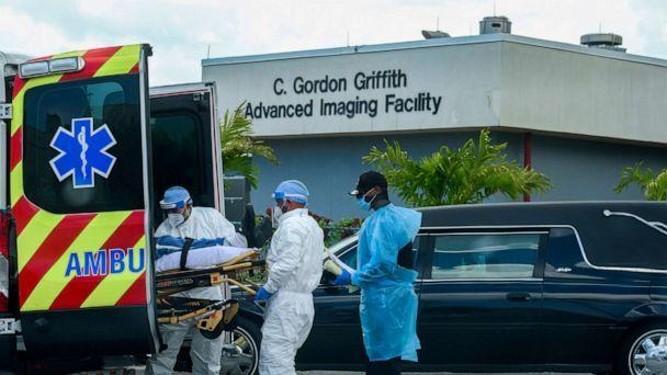 PHOTO: Emergency Medical Technicians arrive with a patient while a funeral car begins to depart at North Shore Medical Center where coronavirus disease patients are treated, in Miami, July 14, 2020. (Maria Alejandra Cardona/Reuters, FILE)