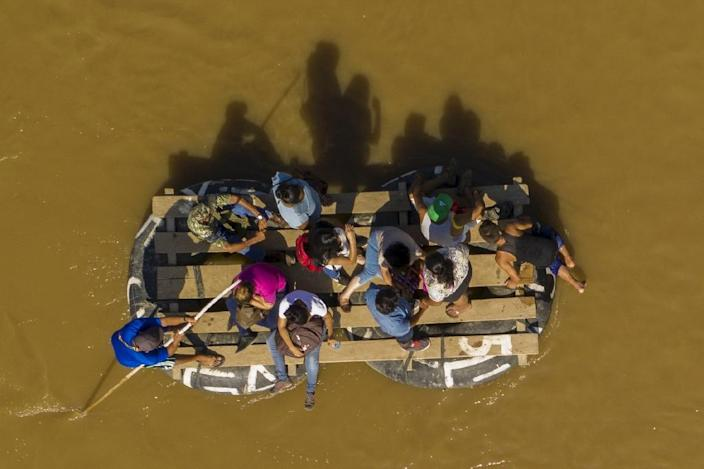 Migrants and residents using a makeshift raft to cross the Suchiate river from Guatemala to Ciudad Hidalgo in southern Mexico (AFP Photo/Pedro PARDO)
