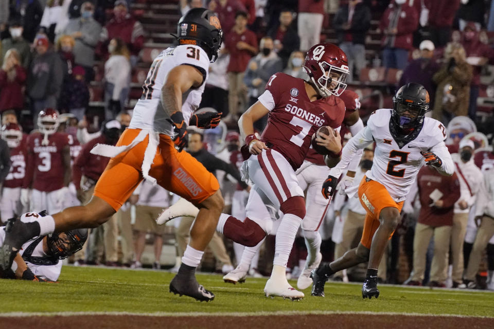 Oklahoma quarterback Spencer Rattler (7) carries for a touchdown, between Oklahoma State's Kolby Harvell-Peel (31) and Tanner McCalister (2) during the first half of an NCAA college football game in Norman, Okla., Saturday, Nov. 21, 2020. (AP Photo/Sue Ogrocki)