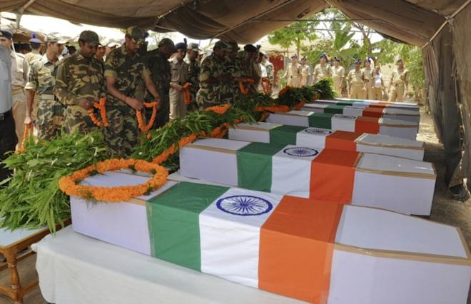 Central Reserve Police Force (CRPF) personnel place garlands on the flag-draped coffins of their colleagues, who were killed in an explosion, during a ceremony in Ranchi May 4, 2011