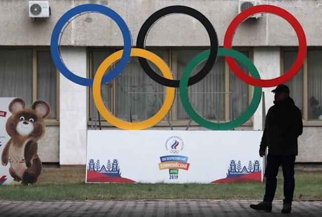 A man stands in front of the Olympic rings outside the headquarters of the Olympic Committee of Russia in Moscow