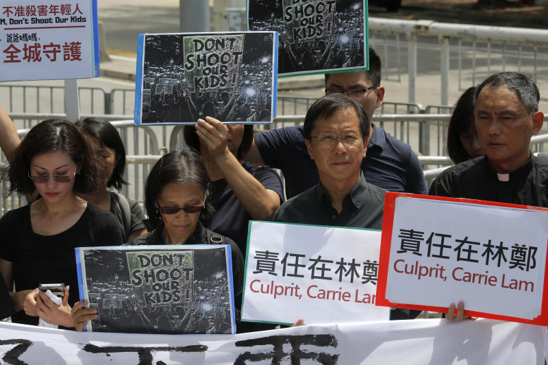 Various of activist groups from parents and religious hold placards outside the government office demanding that stop shooting their kids in Hong Kong, Thursday, June 20, 2019. A Hong Kong student group demanded Wednesday that the city completely scrap a politically charged extradition bill and agree to investigate police tactics against protesters before a Thursday deadline or face further street demonstrations. (AP Photo/Kin Cheung)