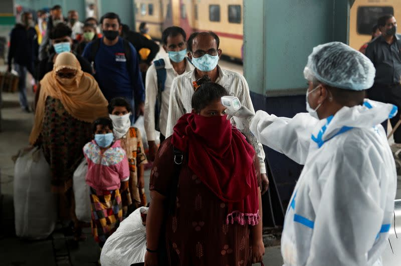 A health worker in personal protective equipment (PPE) checks the temperature of passengers amid the spread of the coronavirus disease (COVID-19), at a railway station in Mumbai