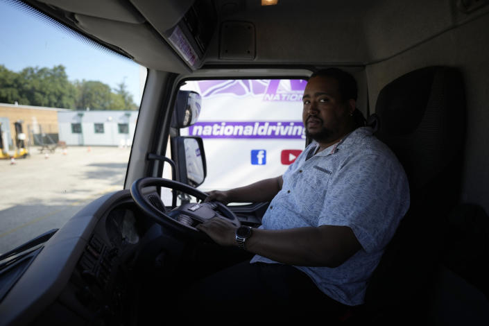 Learner truck driver Cadhene Lubin-Hewitt poses for a portrait in the cab of a truck at the National Driving Centre in Croydon, south London, Wednesday, Sept. 22, 2021. Lubin-Hewitt, 32, moved to the UK when he was 16 from Trinidad and Tobago and has been driving buses and coaches for about 10 years. Britain doesn't have enough truck drivers. The shortage is contributing to scarcity of everything from McDonald's milkshakes to supermarket produce. (AP Photo/Matt Dunham)