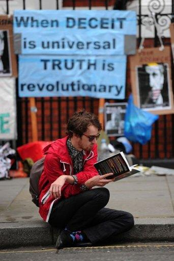 A man reads a book outside the Ecuadorian embassy in London, on June 22, 2012, where Wikileaks founder Julian Assange is seeking political asylum. Assange has said he chose Ecuador's embassy instead of his home country's because he felt Australia had done nothing to protect him, a charge the government has denied