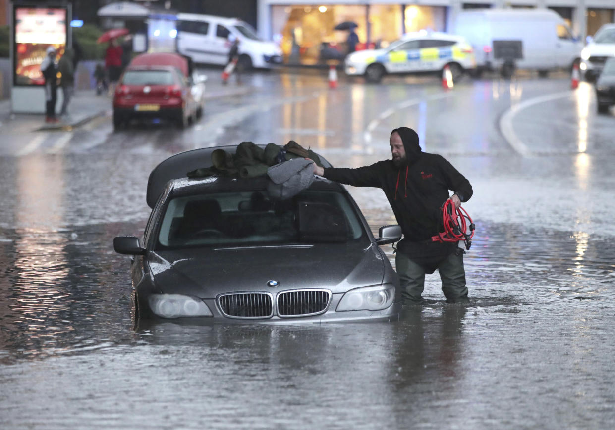 A man gathers items from a car along a flooded street on Thursday in Sheffield after torrential fell rain in the area. (PA)
