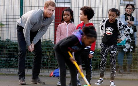 Britain's Prince Harry plays with children as he visits a Fit and Fed school holiday programme - Credit: AP Pool