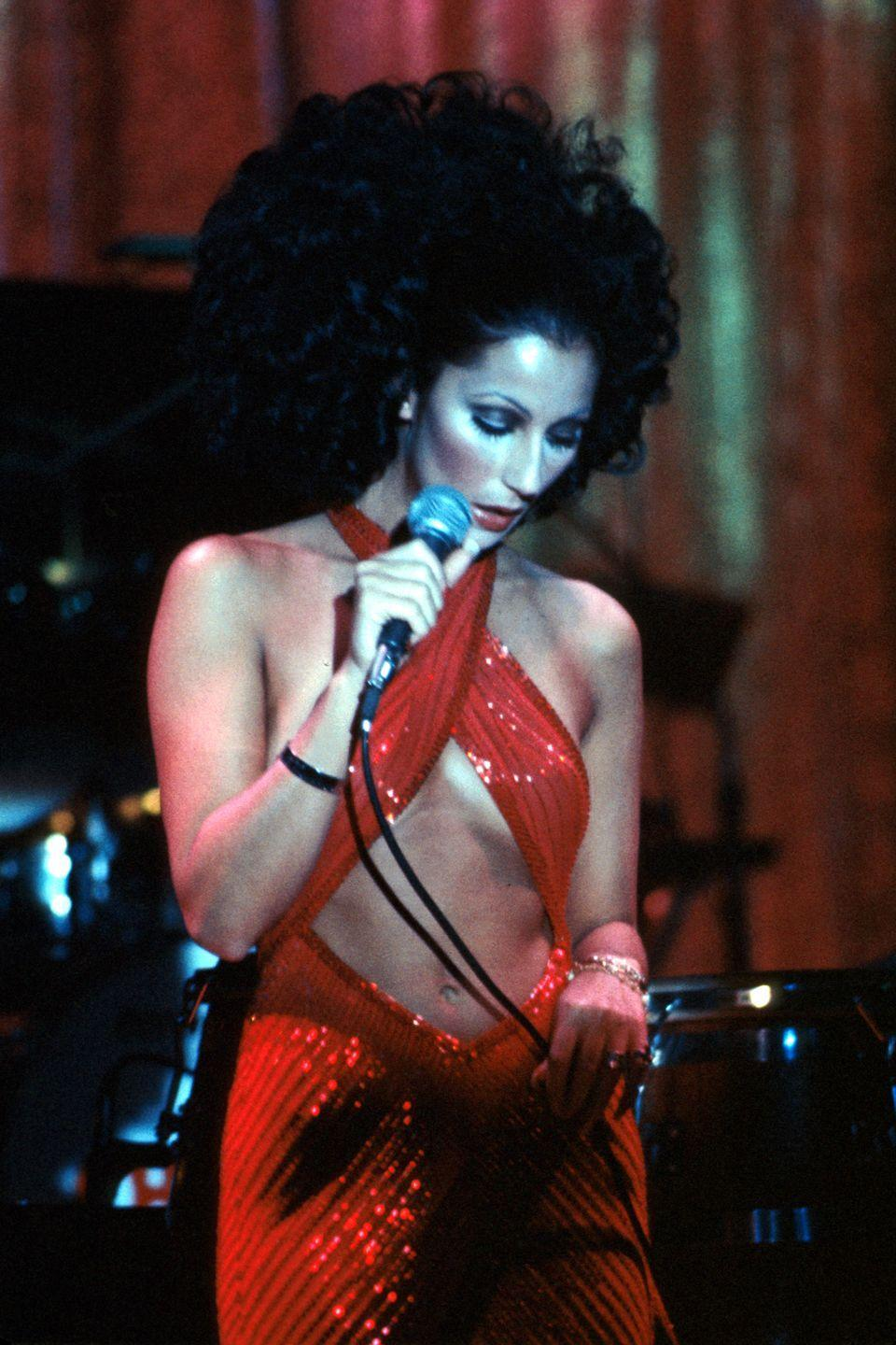 <p>Cher performs onstage in a red-hot number.</p>