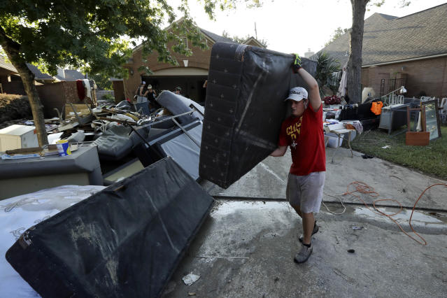 <p>Tyler Moody removes a mattress from a friend's home after floodwaters from Tropical Storm Harvey drenched the city Thursday, Aug. 31, 2017, in Houston. (Photo: Gregory Bull/AP) </p>