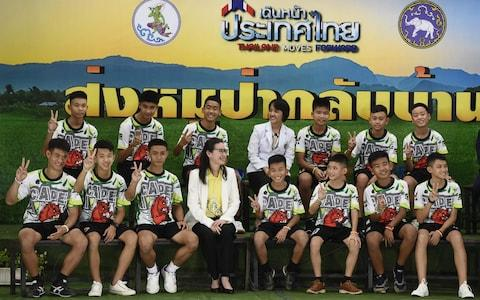 The Twelve Thai boys and their football coach, rescued from a flooded cave after being trapped, attend a press conference in Chiang Rai on July 18, 2018, - Credit: AFP