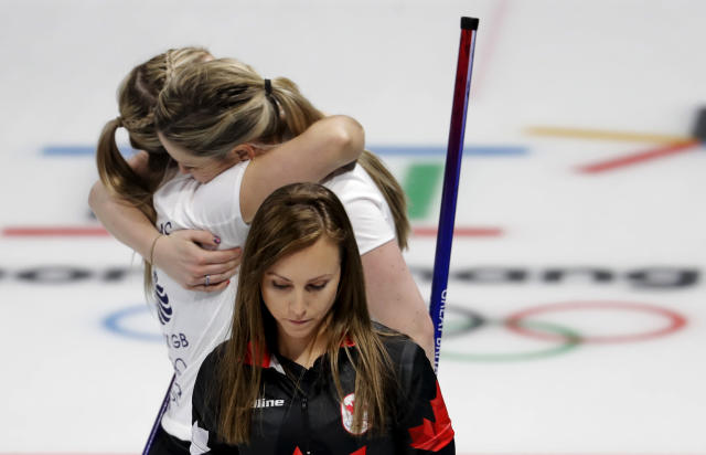<p>Canada's skip Rachel Homan, center, leaves the ice as Britain's Lauren Gray, right above, and Vicki Adams embrace celebrating winning a women's curling match at the 2018 Winter Olympics in Gangneung, South Korea, Wednesday, Feb. 21, 2018. (AP Photo/Natacha Pisarenko) </p>