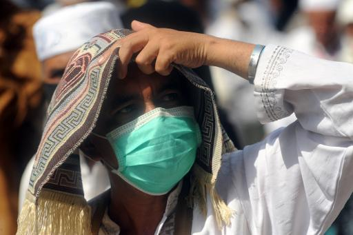 A pilgrim wears a mask during the Friday prayer at Mecca's Grand Mosque, on October 11, 2013 as hundreds of thousands of Muslims pour into the holy city of Mecca for the annual hajj pilgrimage