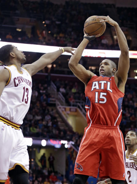 Atlanta Hawks' Al Horford (15) shoots over Cleveland Cavaliers' Tristan Thompson (13) during the first quarter of an NBA basketball game Thursday, Dec. 26, 2013, in Cleveland. (AP Photo/Tony Dejak)