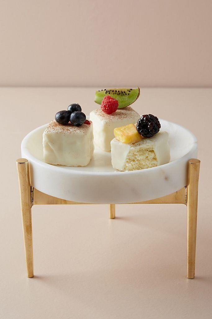 """If they put their desserts on a pedestal, they'll thank you for this cake stand. It's much more modern than the traditional ones you might be used to seeing. This stand is made from marble and brass. <a href=""""https://fave.co/2GwhUK0"""" target=""""_blank"""" rel=""""noopener noreferrer"""">Find it for $58 at Anthropologie</a>."""