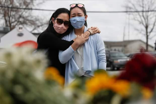 Helen Park Truong, 34, and Sarah Tang, 31, embrace on Friday after laying flowers at a makeshift memorial outside the Gold Spa following the deadly shootings in the Atlanta area. (Shannon Stapleton/Reuters - image credit)