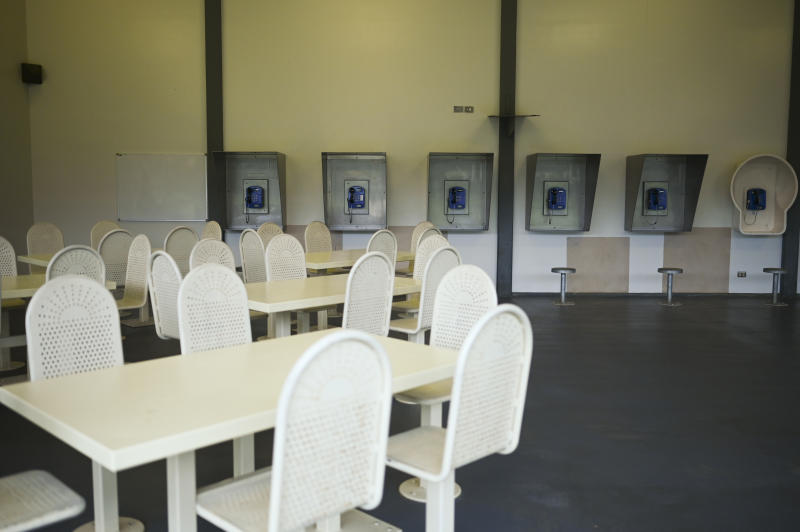 A seated area with telephones on the wall inside the centre. Source: AAP, file.