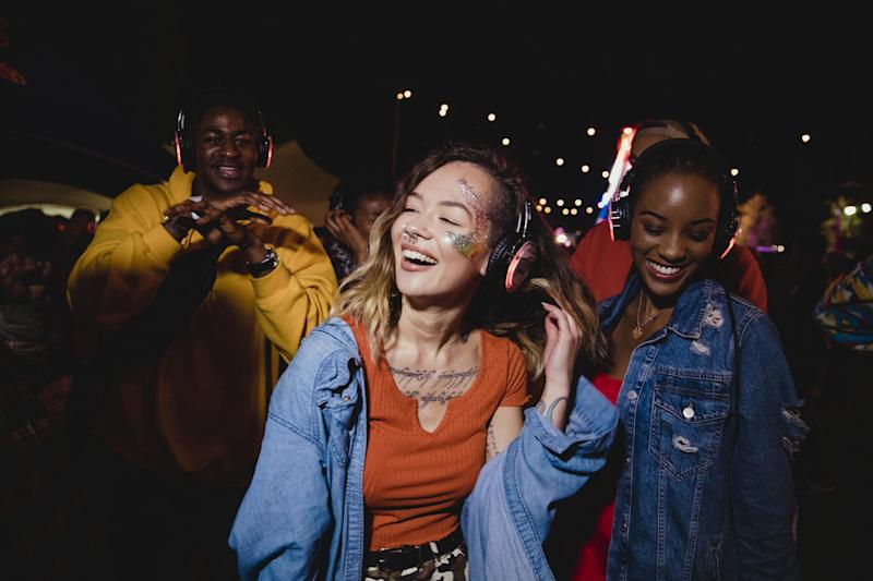 Young woman is dancing in a silent disco with her friends.