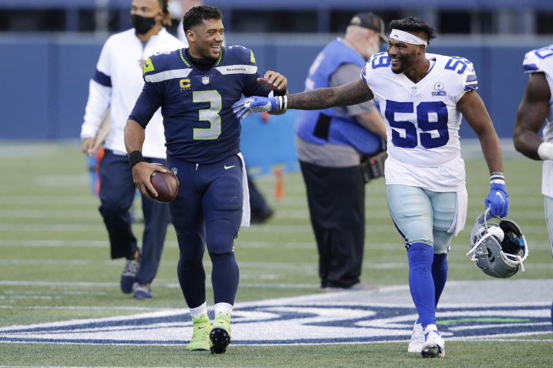 Seattle Seahawks quarterback Russell Wilson (3) greets Dallas Cowboys linebacker Justin March (59) after the Seahawks beat the Cowboys 38-31 in an NFL football game, Sunday, Sept. 27, 2020, in Seattle. (AP Photo/John Froschauer)