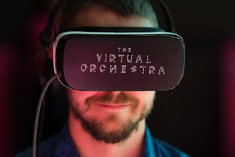 A visitor poses wearing a virtual-reality headset at the Southbank Centre in London experiencing a virtual view of the London Philharmonia Orchestra playing in the Royal Festival Hall