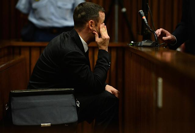 Oscar Pistorius sits in the dock in court in Pretoria, South Africa, Friday, March 14, 2014 on the tenth day of his murder trial proceedings. Pistorius is charged with the shooting death of his girlfriend Reeva Steenkamp, on Valentines Day in 2013. (AP Photo/Phill Magakoe, Pool)